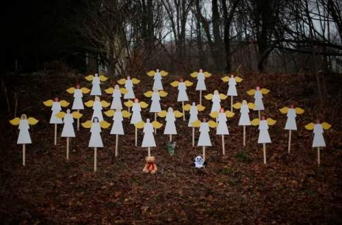 Twenty-seven wooden angel figures are seen placed in wooded area beside road near Sandy Hook Elementary School for victims of school shooting in Newtown, Connecticut